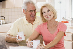 Couple in kitchen with coffee smiling Stock Image