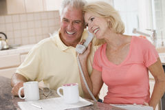 Couple in kitchen with coffee using telephone Stock Photography