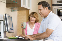 Couple in kitchen with computer and coffee smiling Royalty Free Stock Photo