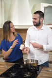 Couple in kitchen cooking together and communicating. Royalty Free Stock Photography