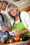 Couple in kitchen cooking together vegetables Royalty Free Stock Photos