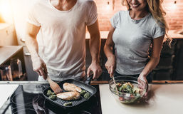 Couple on kitchen. Cropped image of attractive couple is cooking on kitchen Royalty Free Stock Image