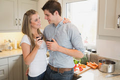 Couple in the kitchen drinking a glass of red wine Stock Photography