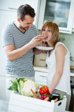 Couple in kitchen, eating bread with tomato. Loving family at home royalty free stock photos