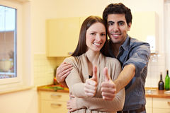 Couple in kitchen holding thumbs up Stock Photo