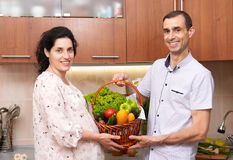 Couple in kitchen interior with basket of fresh fruits and vegetables, healthy food concept, pregnant woman and man Stock Image