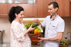Couple in kitchen interior with basket of fresh fruits and vegetables, healthy food concept, pregnant woman and man Stock Images