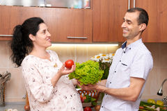 Couple in kitchen interior with basket of fresh fruits and vegetables, healthy food concept, pregnant woman and man Stock Photography