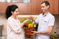 Couple in kitchen interior with basket of fresh fruits and vegetables, healthy food concept, pregnant woman and man Royalty Free Stock Image