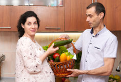 Couple in kitchen interior with basket of fresh fruits and vegetables, healthy food concept, pregnant woman and man Royalty Free Stock Photos
