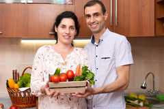 Couple in kitchen interior with box of fresh fruits and vegetables, healthy food concept, pregnant woman and man stock image