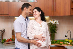 Couple in kitchen interior with fresh fruits and vegetables, healthy food concept, pregnant woman and man Royalty Free Stock Image