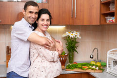Couple in kitchen interior with fresh fruits and vegetables, healthy food concept, pregnant woman and man Stock Images