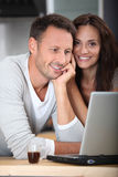Couple in kitchen with laptop computer Stock Photo
