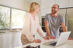Couple in the kitchen with the laptop Stock Photo