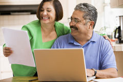 Couple in kitchen with laptop and paperwork Stock Photos