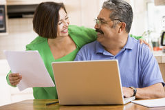 Couple in kitchen with laptop and paperwork Royalty Free Stock Photography