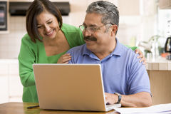 Couple in kitchen with laptop smiling Royalty Free Stock Photos