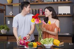 A couple in the kitchen with a lot of fruit and vegetable royalty free stock images