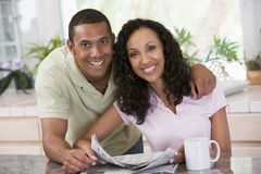 Couple in kitchen with newspaper with a coffee royalty free stock images