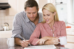 Couple in kitchen with newspaper with coffee royalty free stock photos