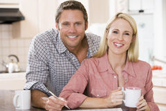 Couple in kitchen with newspaper with coffee Stock Photo
