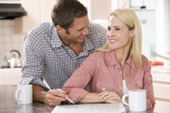 Couple in kitchen with newspaper with coffee Stock Photography