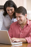 Couple in kitchen with paperwork using laptop Stock Photography