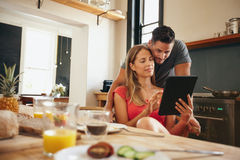 Couple in kitchen sharing an interesting site on digital tablet Stock Photo