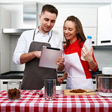 Couple at kitchen with tablet pc Stock Photography
