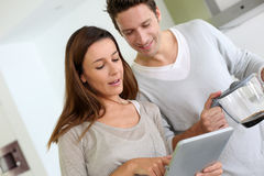 Couple in kitchen using tablet and drinking coffee Royalty Free Stock Photos