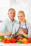 Couple in the kitchen preparing salad Stock Photo