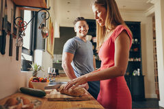 Couple in the kitchen with woman cutting bread. Indoor shot of young men and women in kitchen during morning. Focus on women cutting bread, preparing breakfast Royalty Free Stock Photography
