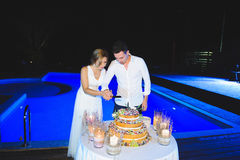 Couple with Knife and Cake. Couple with knife looking at wedding cake on table Royalty Free Stock Image