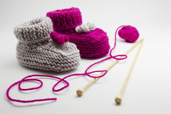 Couple knitted bootees to newborn Stock Images