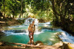 Couple on Kuang Si waterfall. Beautiful young caucasian couple on amazing Kuang Si waterfall near touristic Luang Prabang in Laos. People and landscape of nature Royalty Free Stock Photo