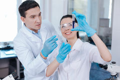 Couple of lab assistants looking at assay reagent. Two experimenters. Serious medical worker wrinkling forehead standing behind his colleague while stretching royalty free stock image