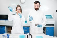 Laboratory assistants working with test tubes. Couple of laboratory assistants in uniform working with analysis in test tubes at the medical laboratory Stock Photography