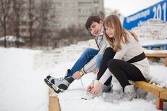 Couple lacing up the skates Royalty Free Stock Photo