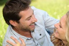 Couple laid on grass. Playful couple laid on grass royalty free stock image