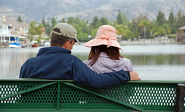 Couple by the Lake - Caring. A couple sit on a bench by a lake, showing care and affection for one another Stock Image