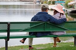 Couple by the Lake - Girl Look. A couple sit on a bench by a lake, the girl looks at her man Stock Image