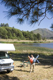 Couple by lake and motor home, man lifting up woman, elevated view Royalty Free Stock Image