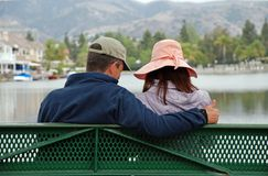 Couple by the Lake - Thumbs Up. A couple sit on a bench by a lake, the man makes the thumbs up gesture Stock Photography