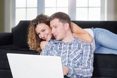Couple with lap top. Happy couple checking lap top in a living room Stock Photos