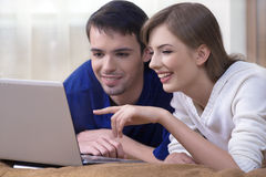 Couple with Laptop. The young couple  have together a rest, look at the laptop screen Stock Photo