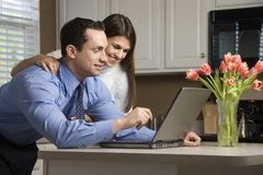 Couple with laptop. Caucasian couple in kitchen with coffee looking at laptop computer Stock Image