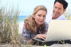 Couple with laptop on beach Royalty Free Stock Photography
