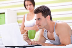 Couple with laptop in bed. Stock Image