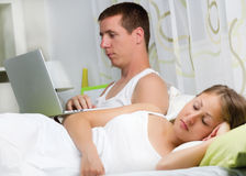 Couple with laptop in bed Stock Photos